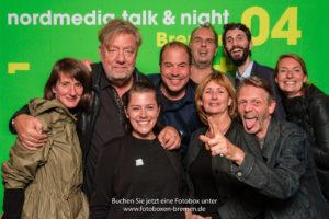 9 Personen fotografieren sich mit der Fotobox vor einer Fotowand auf einer Veranstaltung