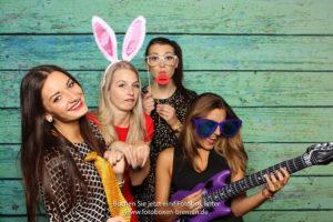 4 Mädchen fotografieren sich mit Luftgitarre und Hasenohren vor einer Fotobox