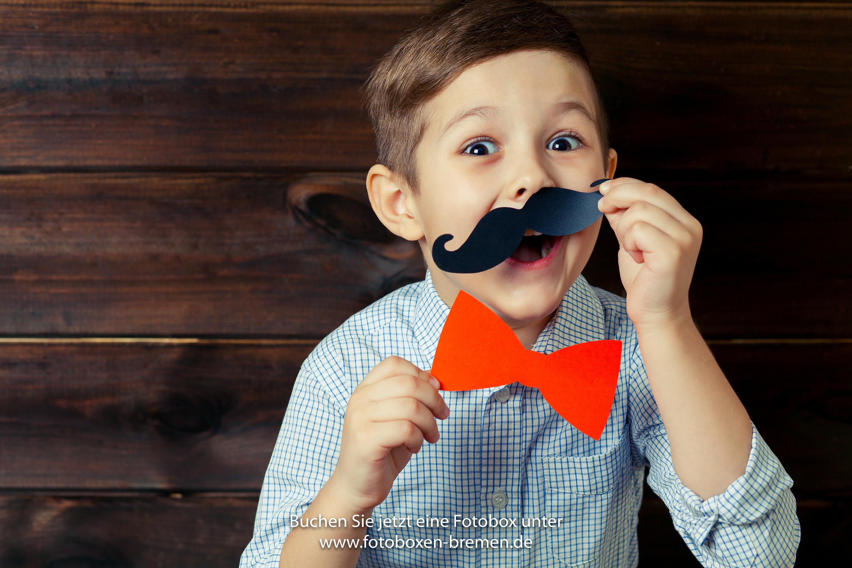 kleiner Junge verkleidet sich mit Props vor der Fotobox