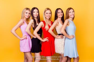 5 Mädchen fotografieren sich vor einem gelben Hintergrund mit einer Fotobox