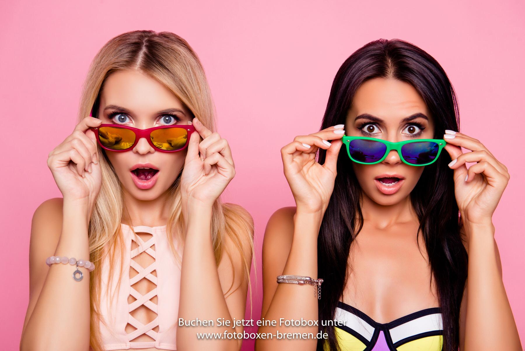 Zwei Frau fotografieren sich mit Sonnenbrillen vor einer Fotobox
