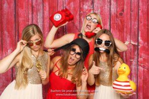 4 Frauen fotografieren sich vor einen Fotobox