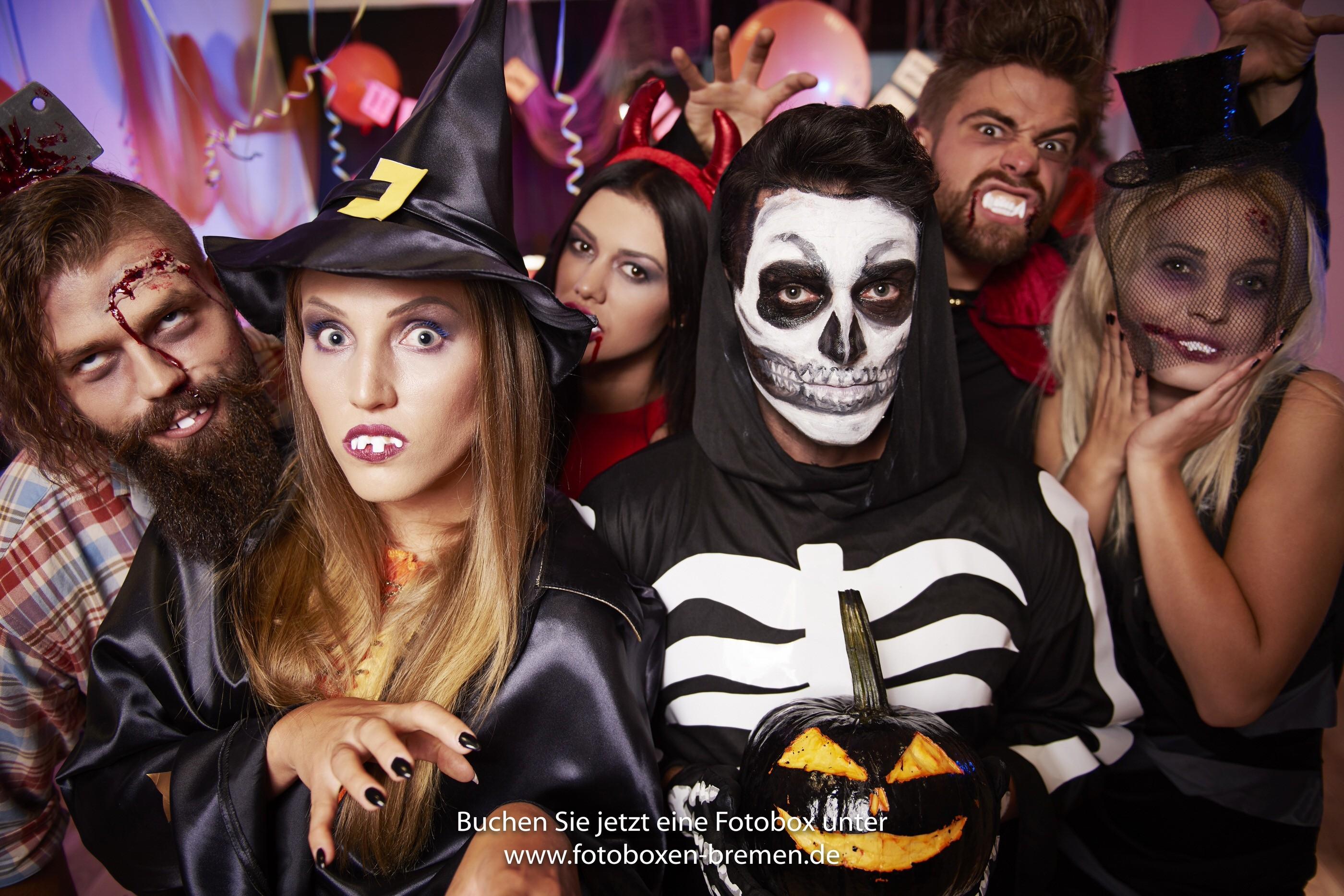Mehrere Leute fotografieren sich in Kostümen auf der Halloween Party vor einer Fotobox