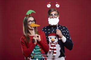 Mann und Frau fotografieren sich vor einer Fotobox auf der Weihnachtsfeier