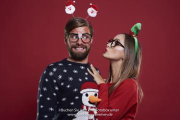 Frau und Mann machen lustige Fotos vor der Fotobox auf der Weihnachtsfeier
