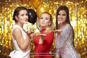 3 Frauen küssen in Richtung Fotobox auf der Silvesterfeier
