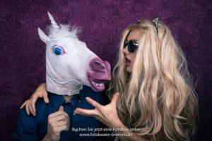 Frau und Mann mit Pferdemaske vor einer Fotobox